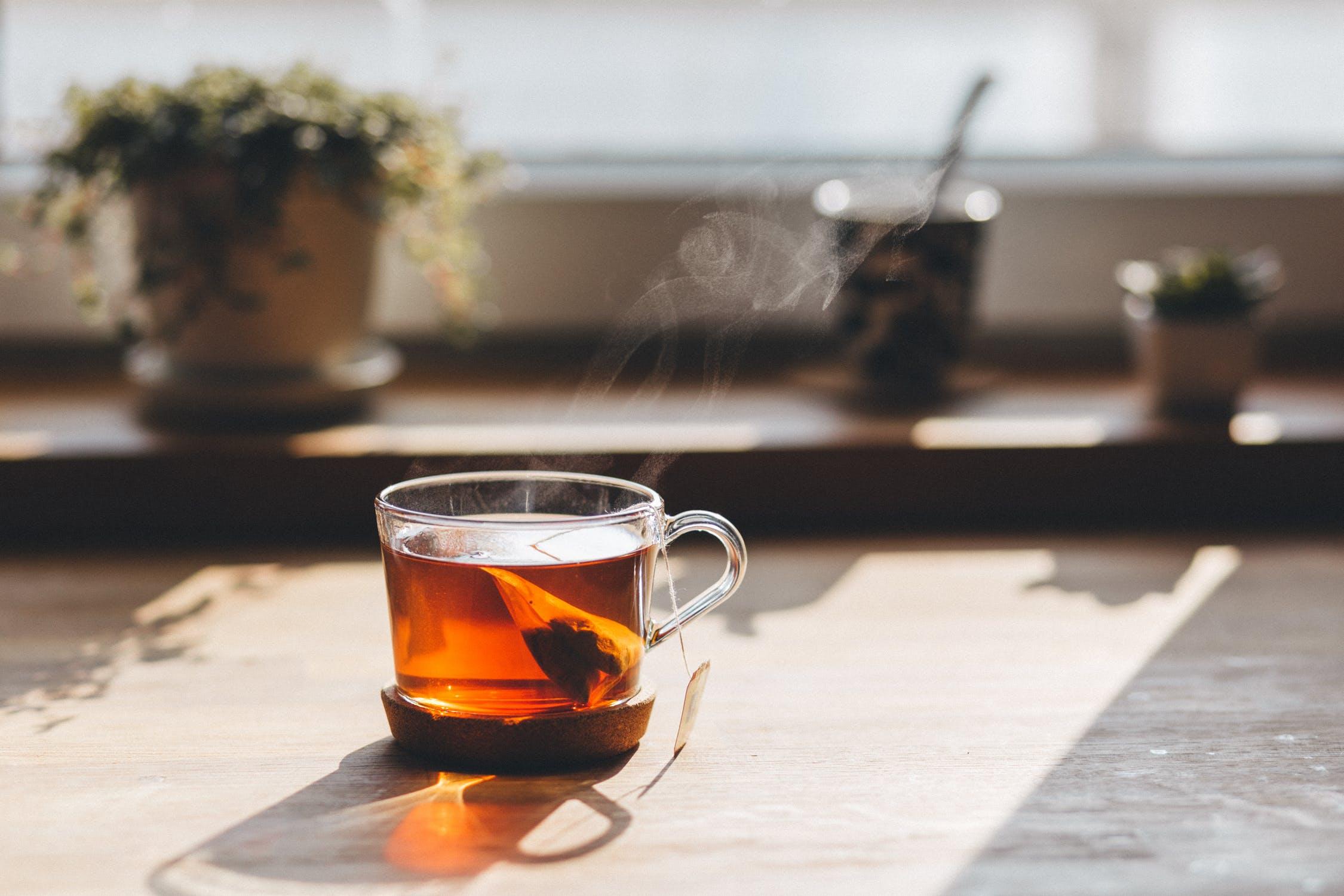透明のカップに入った、紅茶とティーバッグ