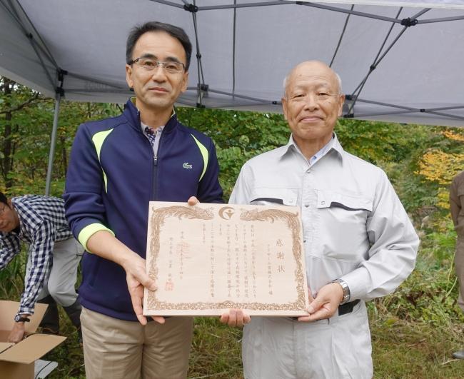 日置郡上市長(右)から感謝状を受け取る代表取締役 専務執行役員の石黒氏(左)