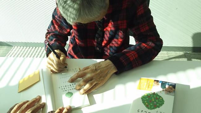 『明日のために、心にたくさん木を育てましょう』(ぴあ)に初めてサインをする若宮正子さん