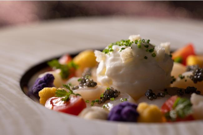 カリフラワーをベースにしたムースソースとキャビアをあしらったホタテのカルパッチョ。ホタテの甘さ、カリフラワーのまろやかな味とキャビアのほどよい塩気が絶妙に合う贅沢な一品。(「Menu de noël 」より)