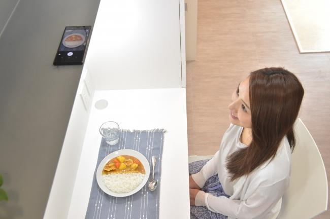 食事するテーブルの上にスマートフォンを置き、食事を撮影。撮影された食事データが自動解析され、メニューを特定し、摂取カロリーや栄養素をアプリに表示