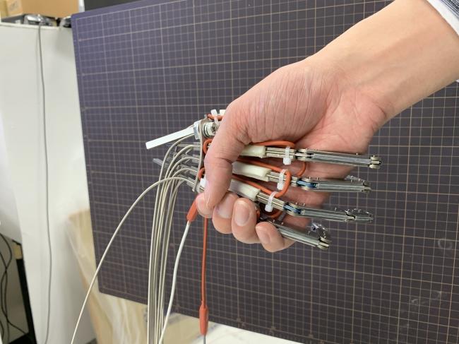 出来上がったロボットハンドと握手する様子。電動モーターで手を握ることが可能。