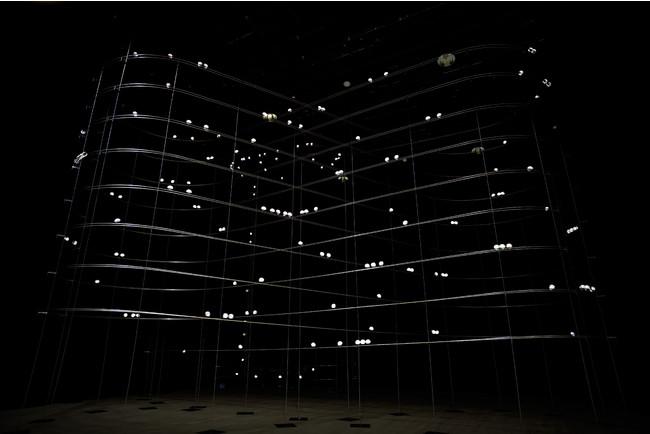 [参考図版] 真鍋大度+石橋素《particles》2011年 写真提供:山口情報芸術センター[YCAM] 撮影:丸尾隆一(YCAM)  構造物の中を走るボールの位置情報を用いてLEDを点滅させ、空中に立体映像を作り出すインスタレーション。