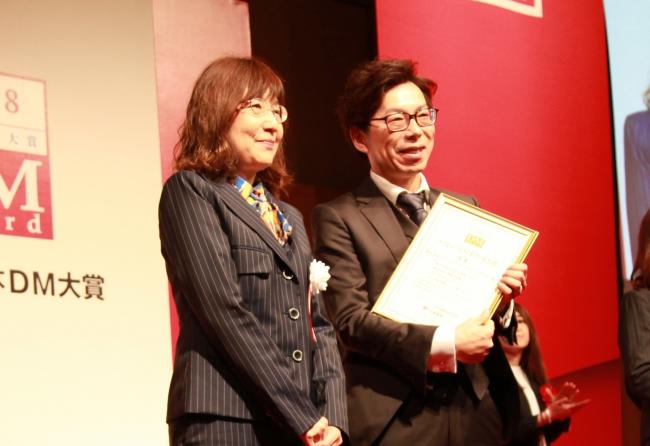金賞を受賞したダイレクトマーケティングゼロ代表・田村(右)。左は審査委員の明石氏。