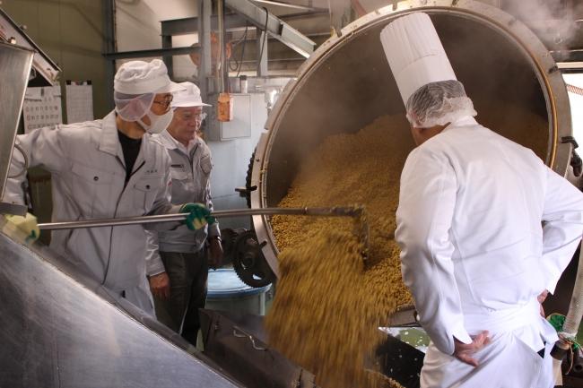 蒸しあがった大豆を糀と混ぜ合わせるために釜から移す様子