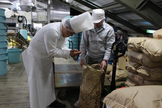 味噌の製造過程を説明する長谷川社長と興味深く質問を続ける鍬先料理長:生の白豆を味わう鍬先料理長