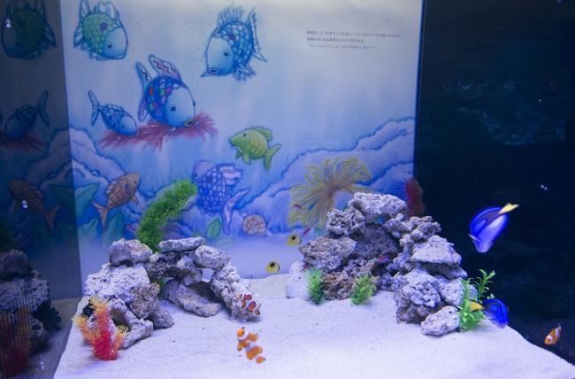 ※水槽の背景に、  シリーズ全8冊の各シーンを設置し、    絵本に登場するキャラクターをイメージした魚を展示