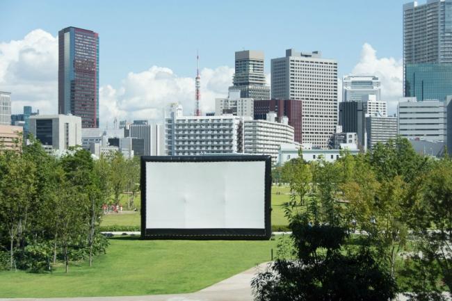 広大な芝生に設置された巨大スクリーン で映画を楽しむ