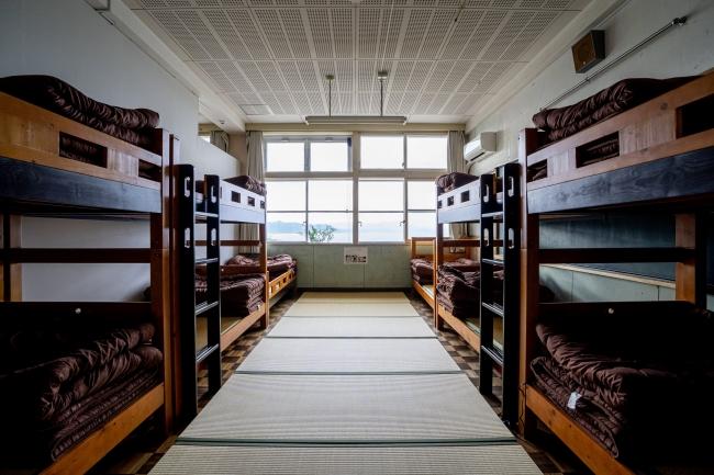 旧教室に2段ベッドが並ぶ大部屋