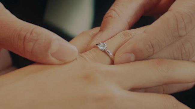 彼女の左手の薬指にエンゲージリングをはめる彼