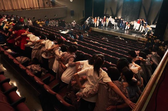 本番前に102人のおとなダンサーと堤監督をはじめとしたスタッフ陣が円陣を組む様子