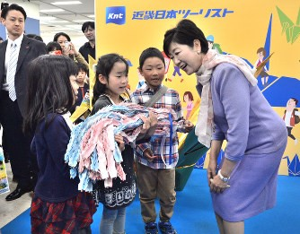 子どもたちから折り鶴を受け取る小池百合子都知事(画像:毎日新聞社提供)