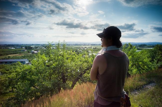 横手盆地を望む丘に広がるりんご畑と園主の佐藤さん
