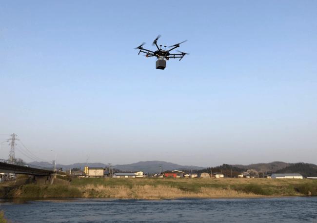 グリーンレーザを搭載したドローンが河川上を飛行する様子
