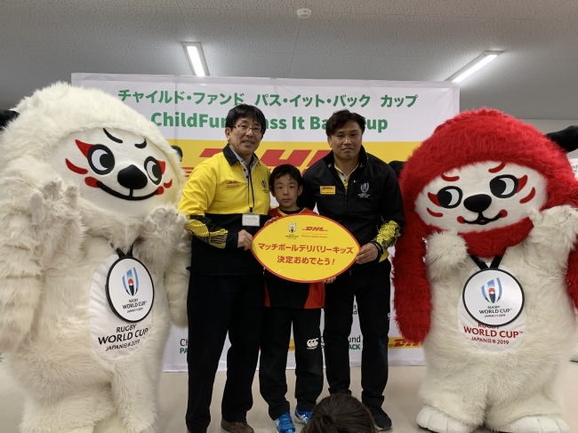 DHLジャパン株式会社セールス&マーケティング本部専務執行役員の片岡康平(左)よりパネルを受け取る上杉翔真君(中央)、 ラグビーワールドカップ2019(TM)におけるDHLアンバサダーを務める大西 将太郎氏(右)と。