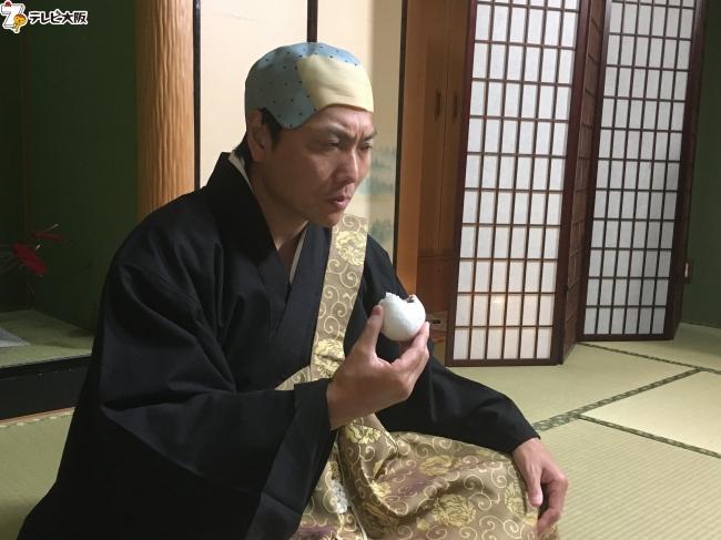 お坊さんの衣装で饅頭をみつめる八木真澄(サバンナ)。饅頭誕生の知られざる秘密とは?