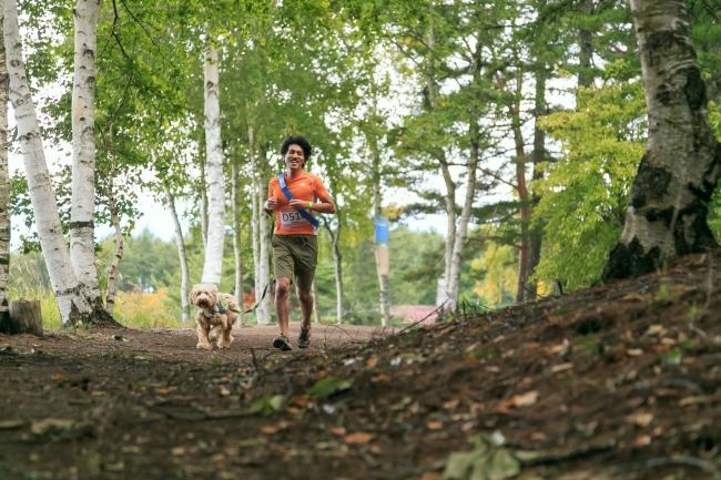 森林の中を愛犬と走るトレイルランニング