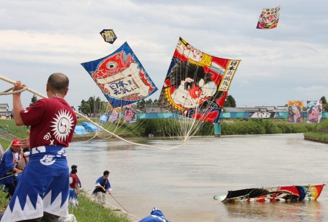 空中で凧を絡ませ川へ叩きつける