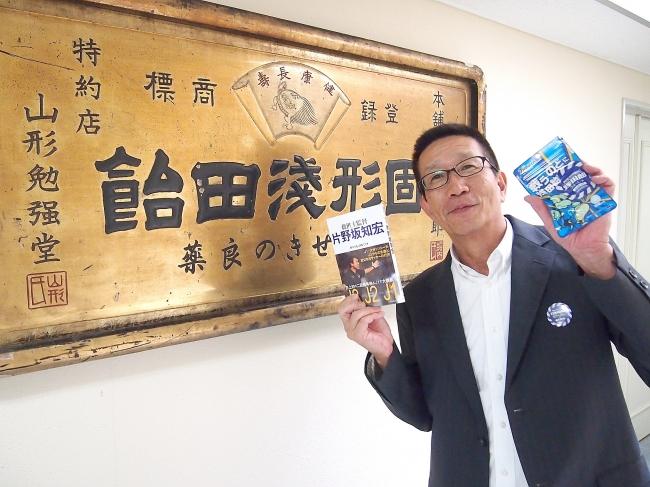 献本された本書を受け取り、浅田飴・堀内邦彦社長もニッコリ
