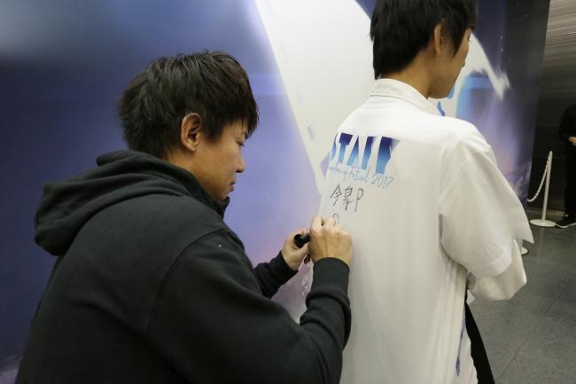 Tシャツにサインをする 今泉プロデューサー