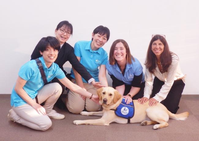 東京都立小児総合医療センターでの実地研修最終試験に合格した、ハンドラー大橋真友子(左から3番目)とファシリティドッグのアイビー。病院への修了報告直後、プロジェクトメンバーとともに。デビューが決まった瞬間。