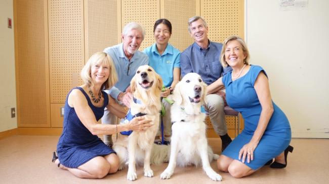 写真5:日本初のファシリティドッグとなったベイリー(写真右)。2018年のベイリー引退セレモニーには、アシスタンス・ドッグス・オブ・ハワイの理事長夫妻(右)、パピーレイザー夫妻(左)が駆けつけた。
