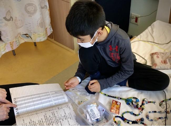 ビーズ・オブ・カレッジ プログラムのビーズを、自分の治療の記録のビーズ日記を確認しながら繋いでいくお子さんの様子