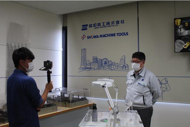 職場見学前に自社で製作する「金型」について説明している昭和精工の木田社長
