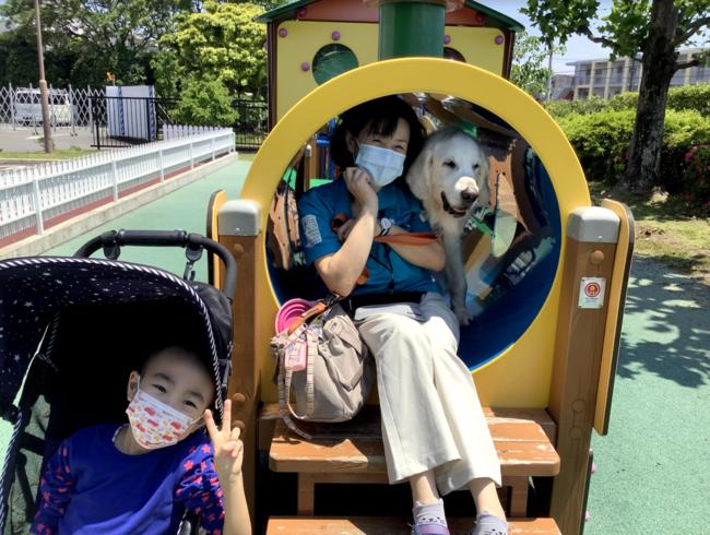 今年の初夏に撮影。前任犬のヨギが入院中のお子さんと病院前の「ぽっぽ広場」でお散歩を楽しむ様子