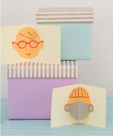 人の顔とマスクやメガネが切り紙のカード。