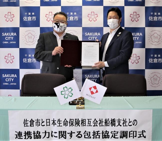 署名済の協定書を掲げる西田佐倉市長(左)、日本生命中山支社長(右)