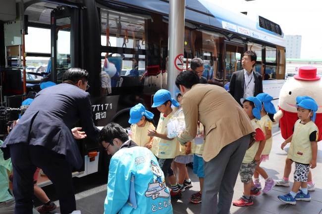燃料電池バスの運行開始を祝って初便搭乗客には記念品が配られた