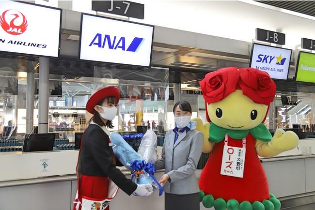 ANAスタッフにバラの花束を手渡すおおの親善大使の宮川さん
