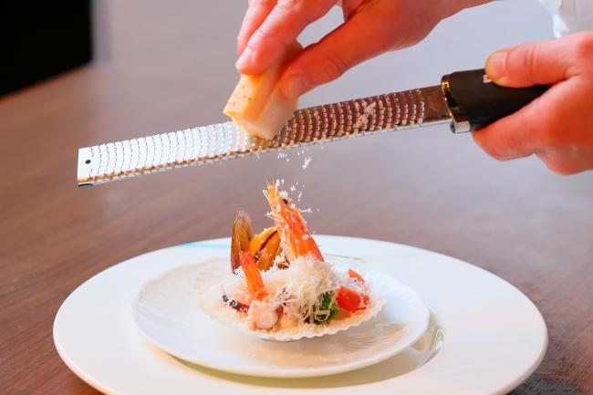 魚介類に3種のチーズを削る