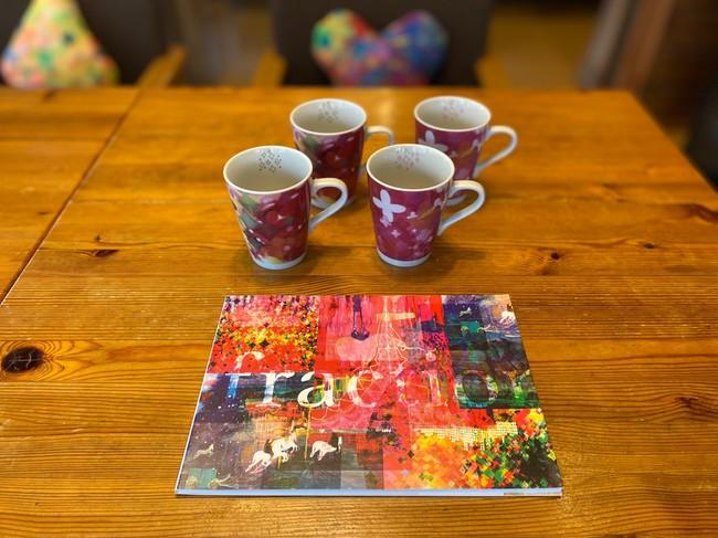 コテージ内のマグカップ、クッション、 持ち帰り可能なアートブックも 越さんのオリジナル作品の一部