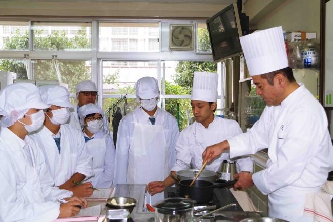 生徒らにフランス料理の調理方法を指導する総料理長の田中 耕太郎