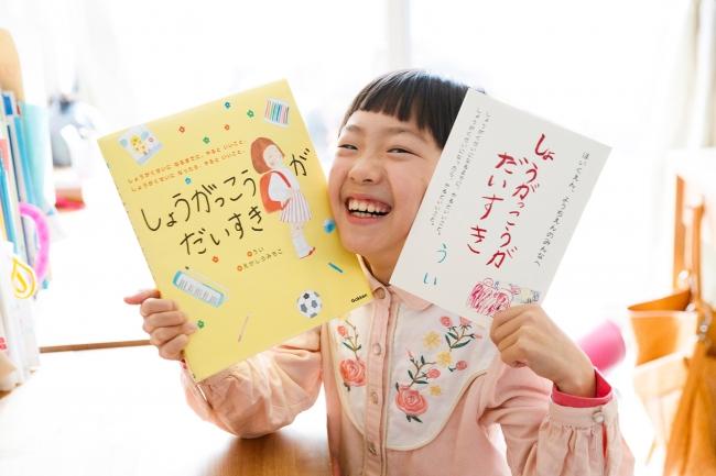 ▲作者のういさん。左手に持っているのが、本絵本の原本となった小冊子です。小学校生活を楽しく、もっと大好きになれるようにとのういさんの希望により、絵本とこの冊子をセットにしてプレゼントします!