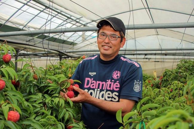 [画像] ライチ農家・森哲也さん。イベントではお客様にライチを手渡し、直接皮をむく手ほどきをすることもあるほどライチを愛している。