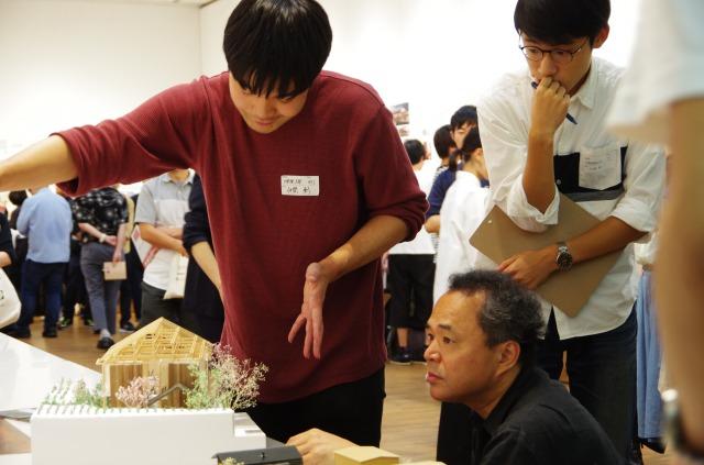 学生の作品を審査する 今年の審査委員長 堀部安嗣氏(写真下)