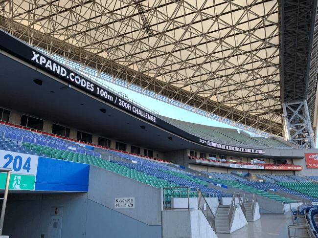 埼玉スタジアムメインスタンド側リボンビジョンへのXPANDコード表示