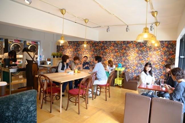 喫茶店の中古家具で揃えた喫茶スペースの向こうに大テーブル、そしてランドリースペースがある