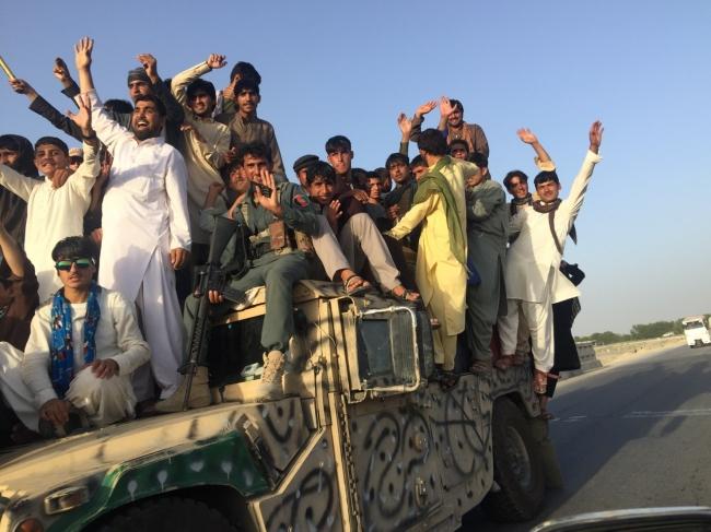 軍の車両に乗って停戦の喜びを表す若者たち