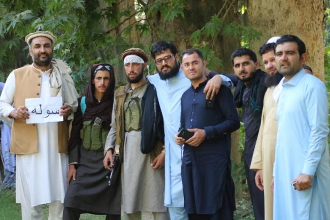 武器を持つタリバン兵士とともに。アフガニスタン現地スタッフ(左端)の手には「平和」の文字