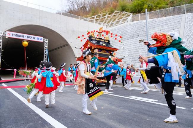 「町道 細浦・柳沢線開通式」には地元でおなじみの八幡大神楽も登場。子どもたちも参加して盛り上げた。