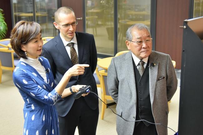 最新の「モンスターハンター:ワールド」を体験する高井美紀MBSアナウンサー(写真左)