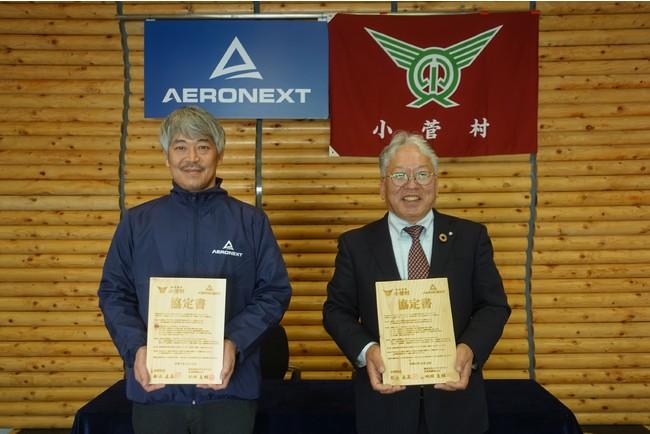 小菅村の木で作られた木版の協定書を掲げる写真向かって左よりエアロネクスト代表取締役CEO田路圭輔、小菅村長舩木直美