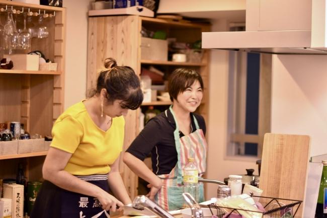 浅草在住のホスト、丸山さん(右)宅でベジタリアン向けの豆腐料理を一緒に作るオーストラリアからの旅行者のアーティーさん(左)