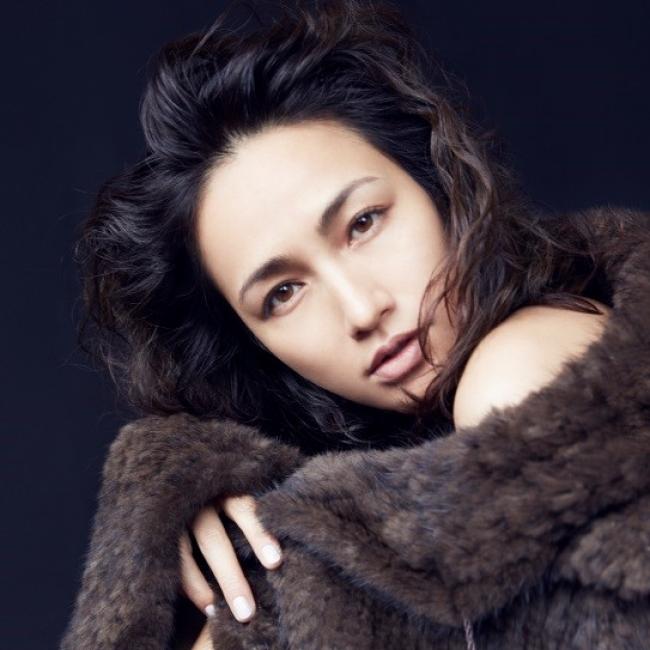 毛皮のコートをまとって座っている佐田真由美の画像