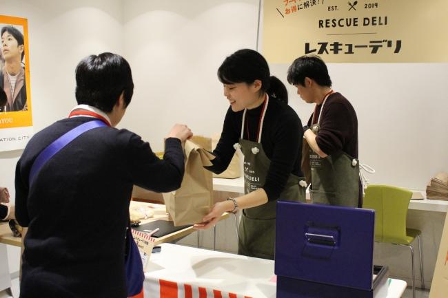 閉店後にレスキューデリの商品を購入する従業員