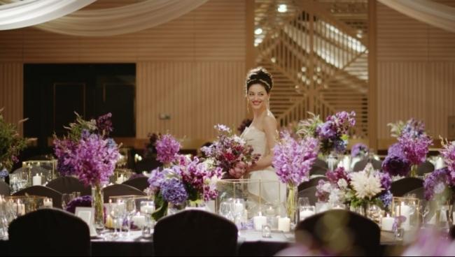 エレガントな紫の花で囲まれた披露宴会場を歩く新婦